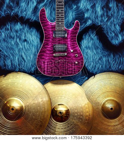 Pink electric guitar with three cymbals on blue faux fur wall. Musical instruments background