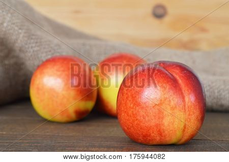 Close up of three nectarines on wooden background