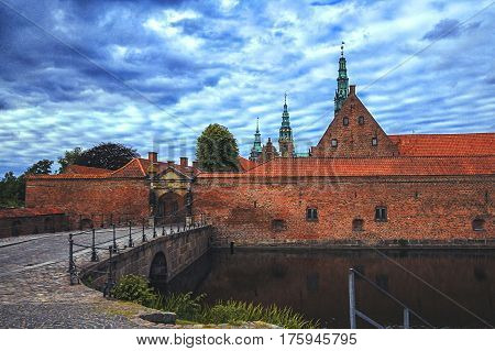 Entrance to Frederiksborg palace Denmark. Red brick fortress wall archway and green copper spiels of towers of renaissance castle Frederiksborg.