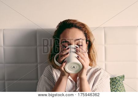 Girl in bed with cup. Need a rush of energy