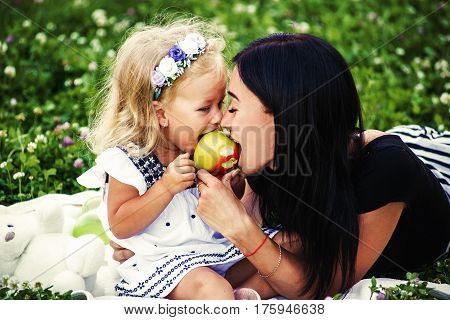 mother and daughter eating an apple in nature. Mother and her child enjoy the early spring, eating apple, happy.
