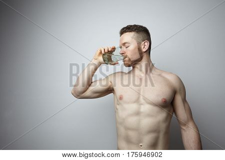 Portrait of young man with perfect boby drinking water