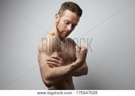 Handsome man with shoulder ache at the white background.