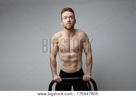 Shirtless muscular athlete doing push-up on push up bars. White background.