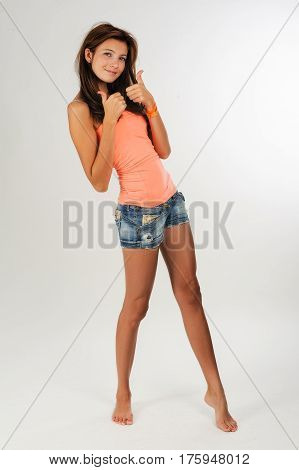 Young beautiful woman with freckles shows thumbs up gesture and looking forward over white background