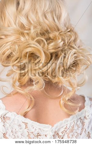 the blonde with a beautiful wedding hairstyle close up. the easy curls on a blonde hair collected in a free bunch. the bride in a lacy wedding dress.