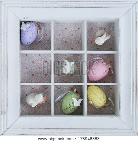Easter tic tac toe game with eggs and rabbits in box clos eup - pastel colors and rustic style