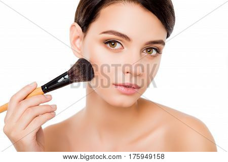 Sensual Young Woman On Isolated White Background  Applying Blusher On Her Cheekbones Using Make-up B