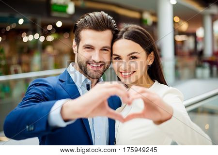 Happy Lovely Young Woman With Her Handsome Boyfriend  In Suit Together Holding And Showing Hands In