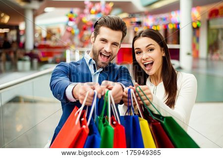 It's Shopping And Fun  Time. Portrait Of Cheerful  Successful Happy Young Lovely Couple Holding  Col