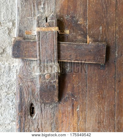 Front view closeup of a wooden aged latch and keyhole over a wooden opened door