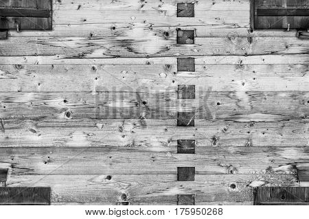Modern Natural Log Cabin Wall Facade Frame Texture. Rustic Log Wall Square Timber Background. Fragment Of Barn Or House Wall From Unpainted Wooden planks Wallpaper. Monochrome.