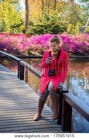 Young woman looks in a smartphone and smiles. Young woman sits on a bridge in in the Keukenhof park among the flowers. Young woman photographer with camera. Young woman in a spring park. Love concept.