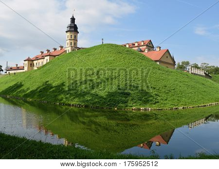 Summer view of the medieval castle of the princes Radziwill and moat from the river in Nesvizh Belarus.