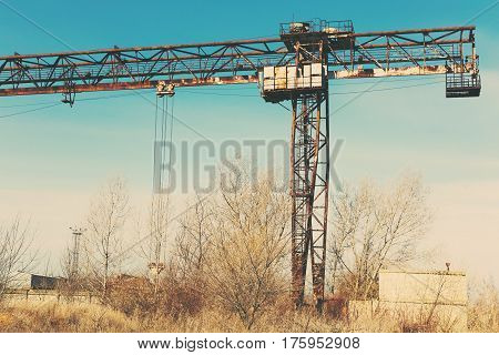 Old rusty gantry crane on railroad an abandoned concrete plant. Crisis collapse of economy and shutdown of production capacities have led to collapse. Global catastrophe. Effect of an old vintage photo.