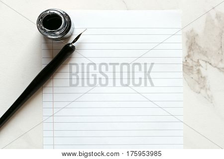 Minimalist desk top with pen and ink, blank lined paper against white marble