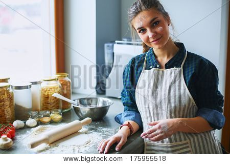 Beautiful woman cooking cake in kitchen standing near desk
