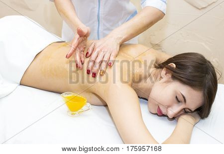 Girl treatment massage honey body wrap in a beauty salon