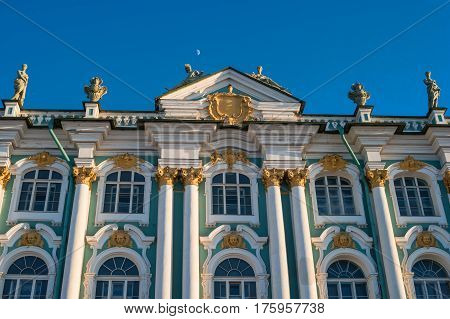 St. Petersburg. Winter Palace. View of the columns and window decor. The moon is visible in the sky.