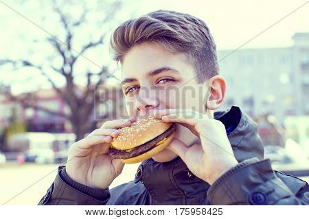 Emotional young guy eating a cheeseburger on the nature