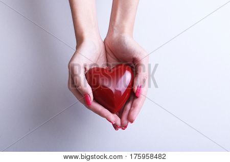 Female doctor hold in hands red heart . Cardio therapeutist, student education, arrhythmia concept.