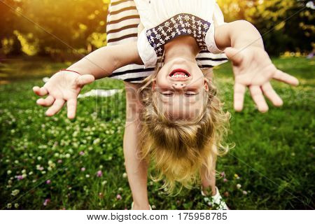 Young mom and cheerful adorable blond tot girl playing, having fun together in park in summertime, mother playfully holding her cute little daughter upside down, close up