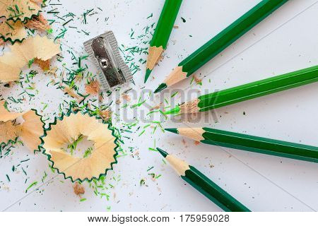 Five Green Colored Pencils And Sharpener On White