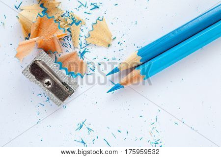 two blue wooden pencils sharpener and blue pencil shavings on white