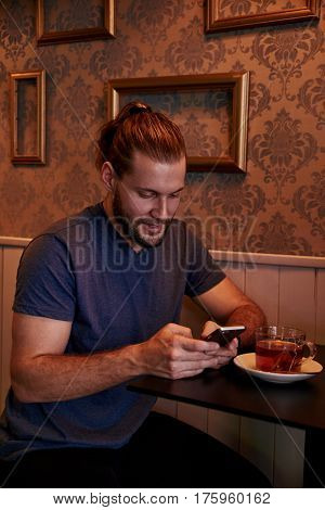 Texting Young Man In A Pub