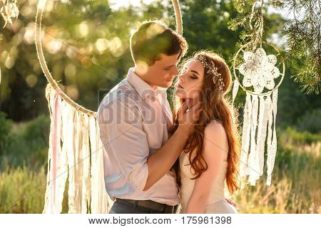 couple in the ears of wheat in forest. The bride and groom in the wheat ears in the Park. Elegant bride and groom together
