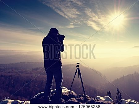Professional Nature Photographer On Snowy Cliff.