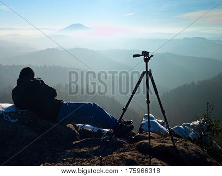 Man Takes Photos With Camera On Sharp Rock. Dreamy Fogy Landscape