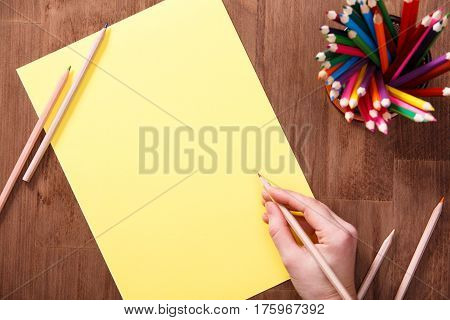 Girl draws with colored pencils on yellow paper on the wooden table. Mockup. Brown background. Bunch of the colorful pencils. Concept. Drawing and painting.