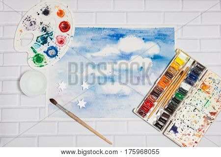 Hand drawn Sketch of Bright Colorful Blue Sky With White Clouds with lying flat paints paintbrushes and palette on the white brick background - concept of human creativity top view