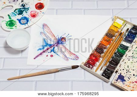 Hand Drawn Bright Sketch of Violet Dragonfly with lying paints paintbrushes and palette on the white brick background - concept of human creativity perspective view