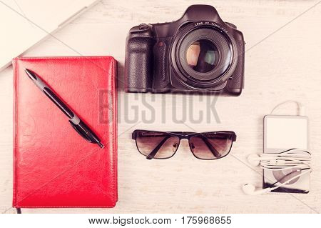 Camera, Laptop, Digital Tabler, Writing Notebook And Sunglasses On Wooden Background