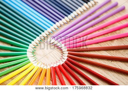 Colourful circle of wooden pencils on brown background, wooden table. Art and design. Artist. Drawing and painting. Concept. School and education.