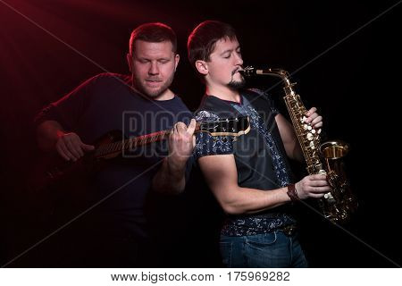 Bearded guitarist with an electric guitar and a saxophonist with a saxophone playfully inspired, isolated on a black background