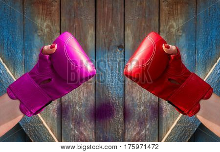 Two female hands in red and pink boxing gloves hands are opposite each other