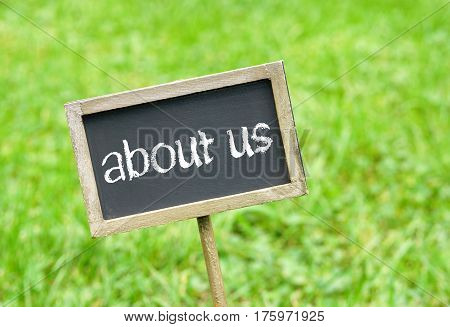 about us - chalkboard with text on green grass background