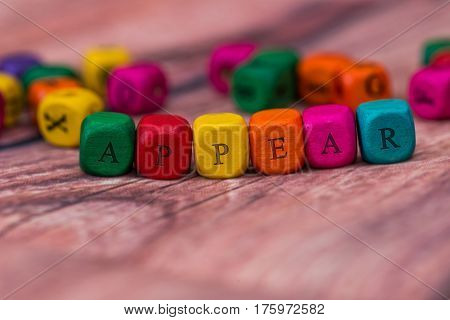 Appear - Word Created With Colored Wooden Cubes On Desk.
