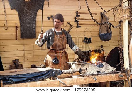 Moscow, Russia - June, 2016: The annual festival in Kolomenskoye. Reconstruction of Ancient Rus. Blacksmith blows the bellows