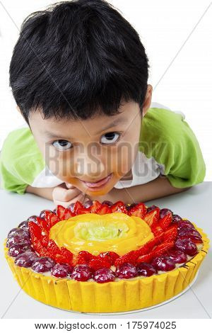 Cute little boy looking at the camera with a delicious pie on the table