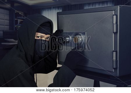 Picture of a male burglar wearing a mask and trying to steal a safe deposit box in the office