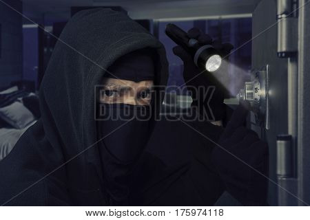 Male burglar holding a flashlight while opening a bank vault in the bedroom at home