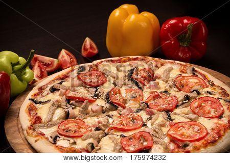 Pizza, mozzarella, pork, onion, bacon, mushrooms, parsley, tomato, garlic on a black background