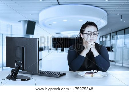 Portrait of Asian businesswoman working with computer while trying to diet and expressing hesitation