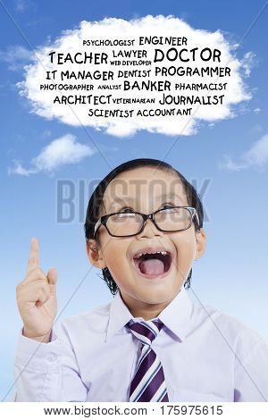Image of elementary student pointing upward while looking at his dreams on the cloud bubble