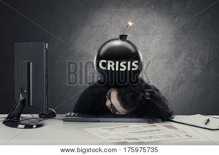 Female entrepreneur sleeping on the keyboard with a bomb of crisis over her head