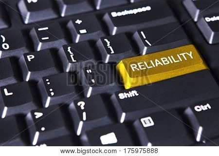 Image of computer keyboard with text of reliability on the golden button